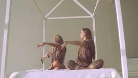 Lyckliga lugna yogakvinnor som öva yoga, poserar i ljus studio arkivfilmer