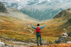 Lyckliga lyftta händer för man med undersökande berg för ryggsäck royaltyfria bilder