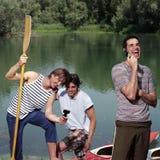 Lyckliga män med kanoten Royaltyfria Bilder