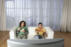 Lyckliga män som håller ögonen på television på soffan  Royaltyfria Foton