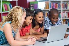 Lyckliga mång- etniska klasskompisar som ser bärbara datorn royaltyfri bild