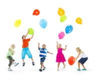 Lyckliga Mång--person som tillhör en etnisk minoritet barn som spelar ballonger Arkivbilder