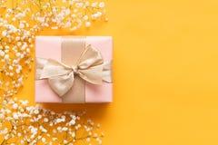lyckliga mödrar för dag Gul och pastellfärgad rosa kulör bakgrund Plant lekmanna- hälsa kort med den härliga gåvaasken royaltyfri foto