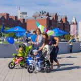 Lyckliga mödrar med ungar i barnvagn som går i Centralet Park under aktivitet för stadsdaglokal Arkivbild