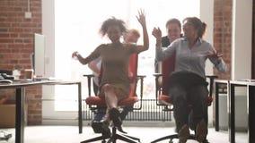 Lyckliga m?ngkulturella kontorsarbetare som skrattar ha gyckel som rider p? stolar