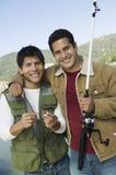 Lyckliga Male vänner som tillsammans fiskar Royaltyfri Foto