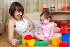 Lyckliga mamma- och ungelekleksaker hemma Royaltyfri Bild