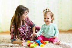 Lyckliga mamma- och ungelekleksaker hemma Fotografering för Bildbyråer