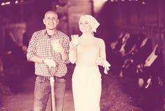 Lyckliga man- och kvinnabönder som står med, mjölkar Royaltyfri Foto