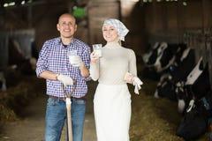 Lyckliga man- och kvinnabönder som står med, mjölkar Royaltyfri Fotografi