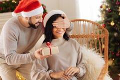 Lyckliga manbeläggningögon av frun och att ge hennes gåva Arkivfoto