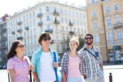 Lyckliga manliga och kvinnliga vänner som går på stadsgatan royaltyfri fotografi