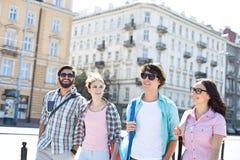 Lyckliga manliga och kvinnliga vänner som går på stadsgatan royaltyfria bilder