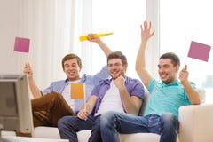 Lyckliga manliga vänner med flaggor och vuvuzela Arkivbild