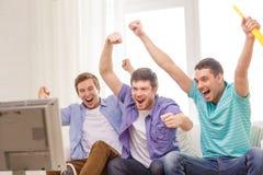 Lyckliga manliga vänner med hållande ögonen på sportar för vuvuzela arkivbilder