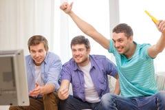 Lyckliga manliga vänner med hållande ögonen på sportar för vuvuzela Fotografering för Bildbyråer