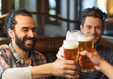 Lyckliga manliga vänner som dricker öl på stången eller baren fotografering för bildbyråer