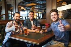 Lyckliga manliga vänner som dricker öl på stången eller baren arkivbild
