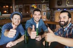 Lyckliga manliga vänner som dricker öl på stången eller baren Arkivfoto
