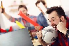 Lyckliga manliga vänner som hurrar och håller ögonen på sportar på tv arkivfoton