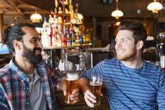 Lyckliga manliga vänner som dricker öl på stången eller baren Royaltyfria Bilder