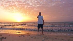 Lyckliga manvisningtummar upp på havsstranden medan morgonsolnedgång i himmel lager videofilmer