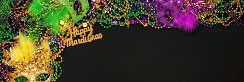 Lyckliga Mardi Gras med lilor, guld, och gröna Mardi Gras pärlor och maskeringar royaltyfri fotografi