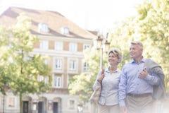 Lyckliga medelåldersa par som går i stad arkivfoto