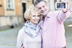 Lyckliga medelåldersa par som tar selfie till och med den smarta telefonen i stad arkivfoton