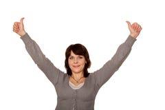 Lyckliga medelåldersa kvinnavisningtummar up tecknet Fotografering för Bildbyråer