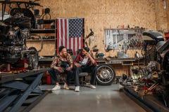 lyckliga mekaniker som har lunch tillsammans royaltyfri foto