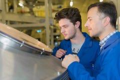 Lyckliga mekaniker som kontrollerar maskinresultat royaltyfria foton