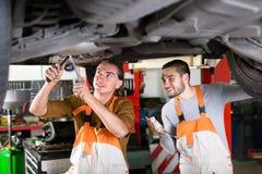 Lyckliga mekaniker som reparerar avgasrörsystemet arkivbilder