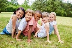 Lyckliga mellan skilda raser barn som vänner arkivbild