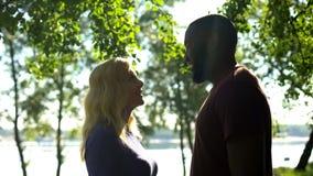 Lyckliga mellan skilda raser par som ser de, kännande förälskelse, förtroendeförhållande arkivbild
