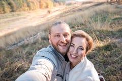 Lyckliga mellersta ålderpar gör selfie utomhus arkivfoton