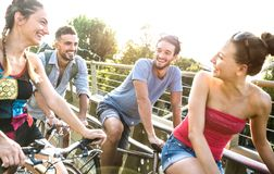 Lyckliga millenial vänner som har den roliga ridningcykeln i stad, parkerar - kamratskapbegrepp med ungt millennial cykla för fol royaltyfri bild