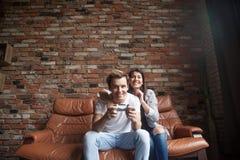 Lyckliga millennial par som hemma spelar videospel royaltyfri foto