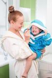 Lyckliga moder- och barntänder som borstar i badrum arkivfoto