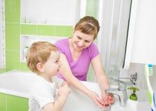 Lyckliga moder- och barntvagninghänder med tvål tillsammans royaltyfria bilder