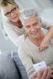 Lyckliga moderiktiga höga par genom att använda smartphonen royaltyfria foton