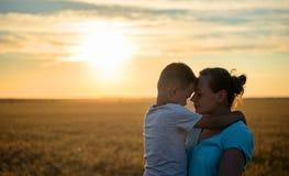 Lyckliga moderkyssar på pannan behandla som ett barn hållande på ett vetefält i solljus, familj i ett vetefält på solnedgången Royaltyfria Bilder