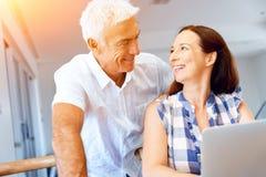 Lyckliga moderna mognar par som hemma arbetar på bärbara datorn royaltyfria foton
