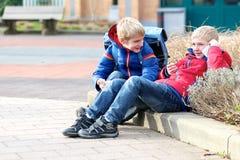 Lyckliga moderna pojkar med mobiltelefonen Royaltyfri Fotografi