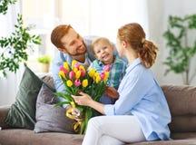 Lyckliga moders dag! fadern och barnet gratulerar modern på ferie arkivfoton