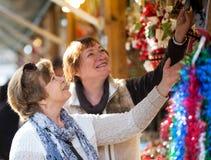 Lyckliga mogna kvinnor som inhandlar julpynt Arkivfoton