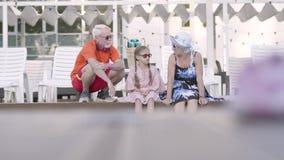 Lyckliga mogna par med den lilla sondottern på kanten av den lyxiga pölen Farmor, farfar och barnbarn stock video