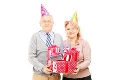 Lyckliga mogna par med födelsedaghattar som rymmer gåvor Arkivfoton