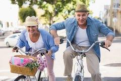 Lyckliga mogna par som går för en cykel, rider i staden Arkivbild