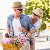 Lyckliga mogna par som går för en cykel, rider i staden Fotografering för Bildbyråer